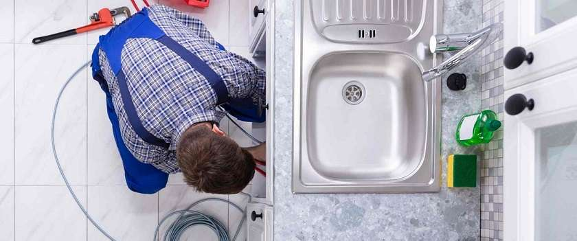 Young Male Plumber Cleaning Clogged Sink Pipe In Kitchen